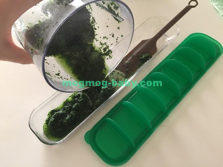 ミキサーでペーストにした小松菜を容器に入れている
